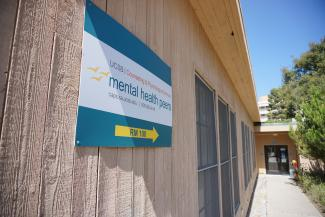 Mental Health Peers Sign pointing towards MHP Office door.